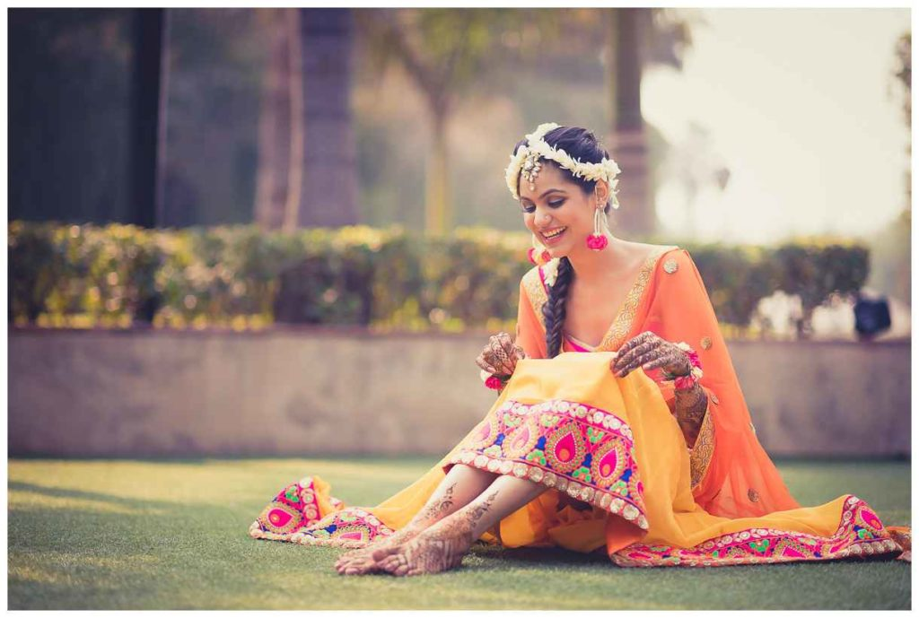 Beautiful mehendi pose of a bride with a bright smile