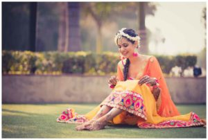 Smiling Bride sitting in the garden area with mehndi in her hands and foot
