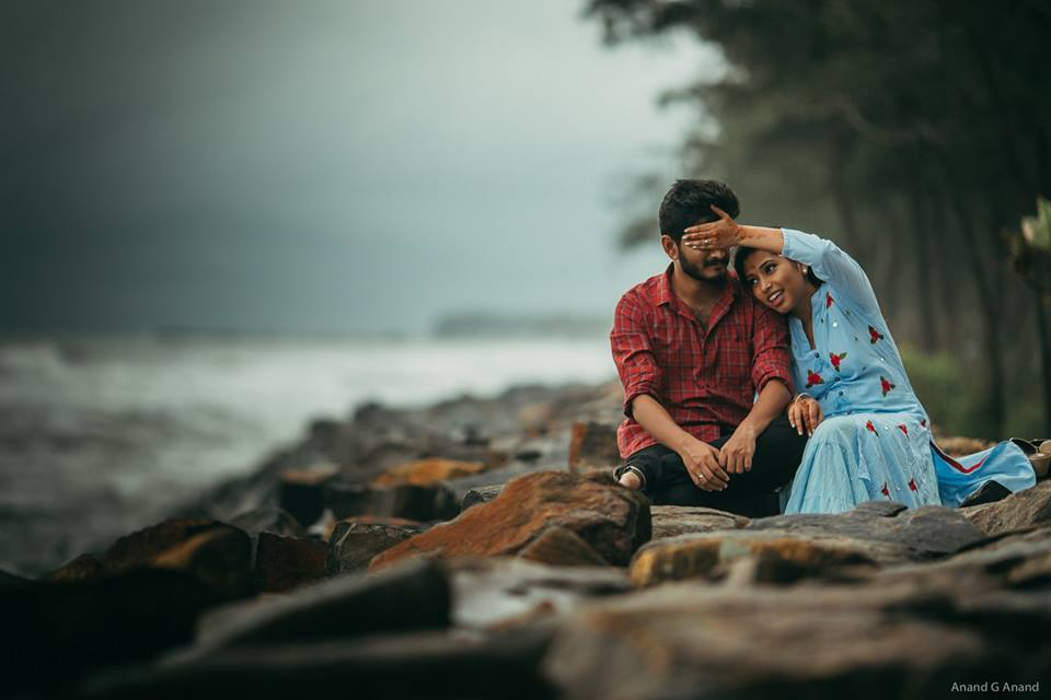 Young couple sitting in the beach side & enjoying their pre-wedding photoshoot