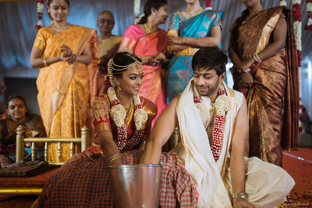 Tamil brahmin Couple enjoying traditional wedding rituals clicked by our candid wedding photographer