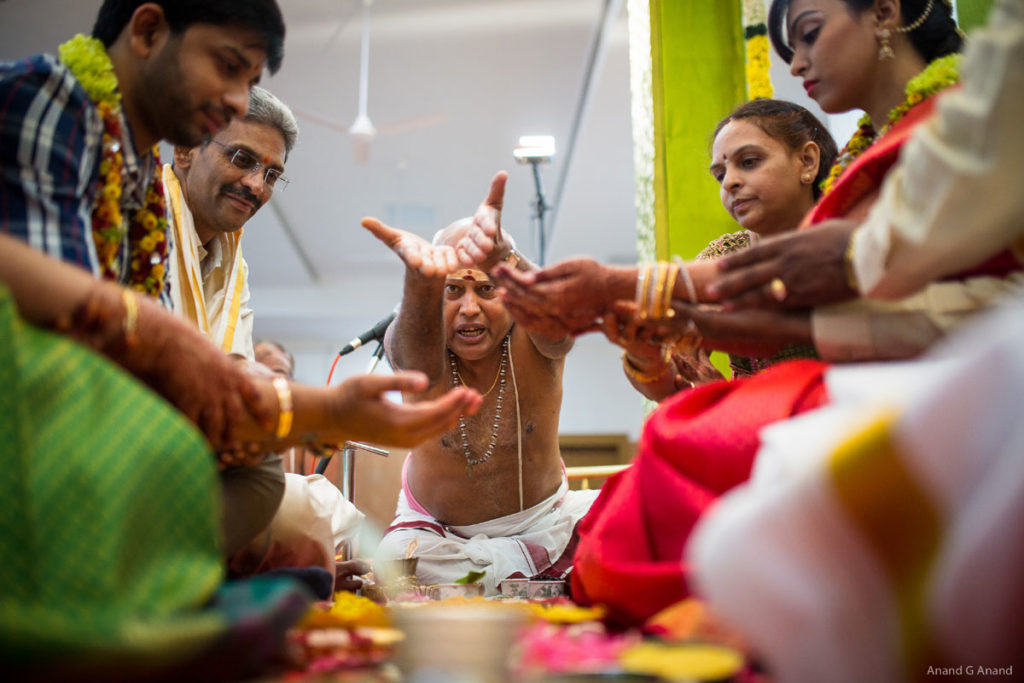 Young couple following traditional brahmin wedding ritual with their parents