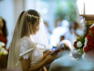 Beautiful young bride weaing white dress reading bible at church